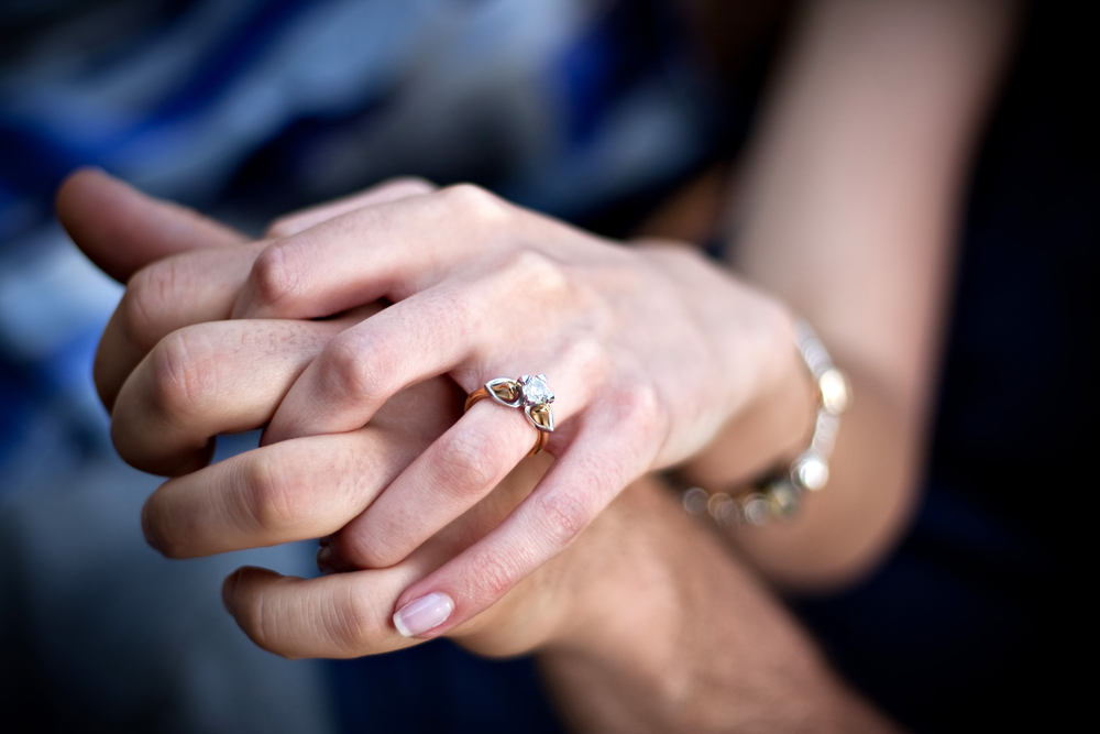 Female wearing engagement ring - holding hands